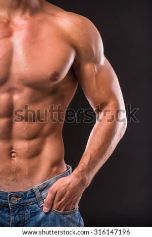 Healthy muscular man isolated on dark background.
