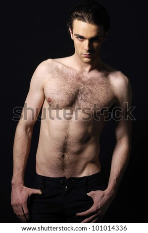 Healthy muscular young man. Isolated on black background. - stock photo