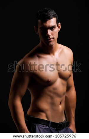 Healthy muscular young man. Isolated on black background.  Shallow DoF with focus on face. - stock photo