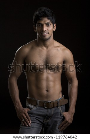 Healthy muscular young man on dark background. - stock photo