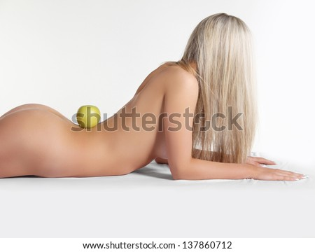 Healthy naked woman body with fresh apple over white - stock photo