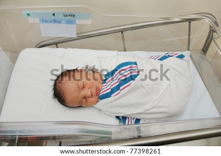 Healthy Newborn Infant Baby Boy Sleeping in Acrylic Hospital Bassinet Wrapped in Pink White Blue Blanket Just after birth - stock photo