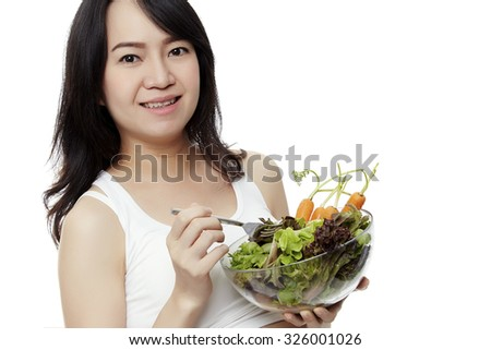 Healthy nutrition and pregnancy. Close-up pregnant woman's belly and vegetable salad. - stock photo