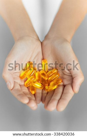 Healthy Nutrition. Cod Liver Oil Omega 3 Gel Capsules - Woman Hand With Vitamins And Dietary Nutritional Supplements. Sport And Diet Concept. Fish Oil Capsules. Health Care, Lifestyle. - stock photo