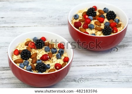 Healthy oatmeal with wild strawberries, blueberries, blackberries and almonds   for breakfast