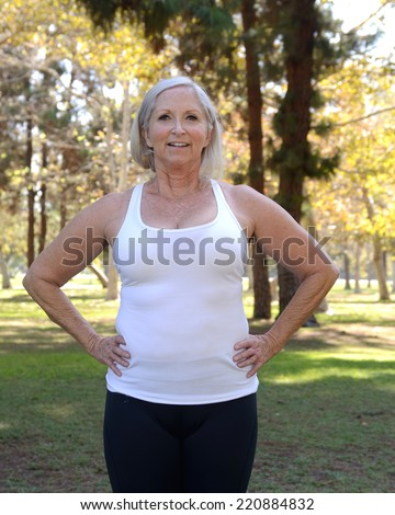 Healthy older woman in park setting/Health Senior Woman/Mature woman exhibits health - stock photo