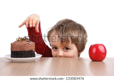Healthy or unhealthy eating little boy choosing between a cake or an apple - stock photo