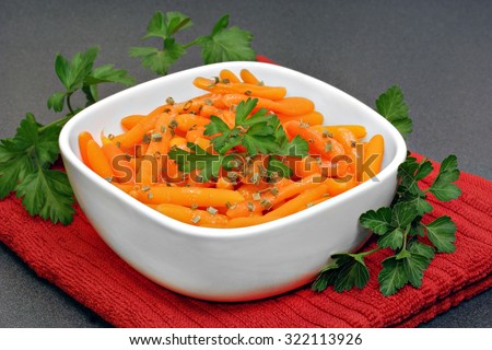 Healthy, organic baby carrots in a bowl garnished with parsley. - stock photo