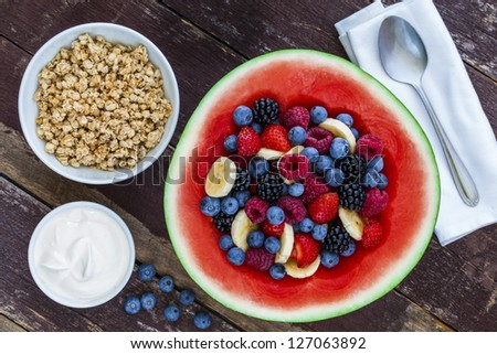 Healthy organic fruit salad in carved watermelon with granola and yogurt - stock photo