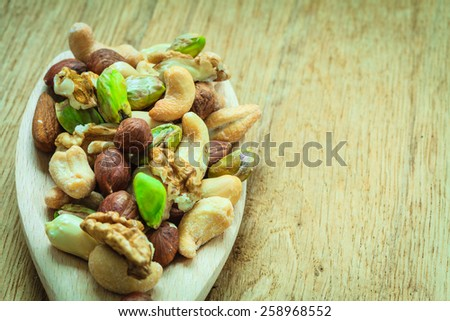 Healthy organic nutrition high fatty acids food and cuisine. Closeup varieties assortment mix of nuts on wooden spoon. - stock photo