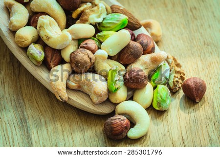 Healthy organic nutrition high fatty acids food and cuisine. Closeup varieties assortment mix of nuts on wooden spoon.