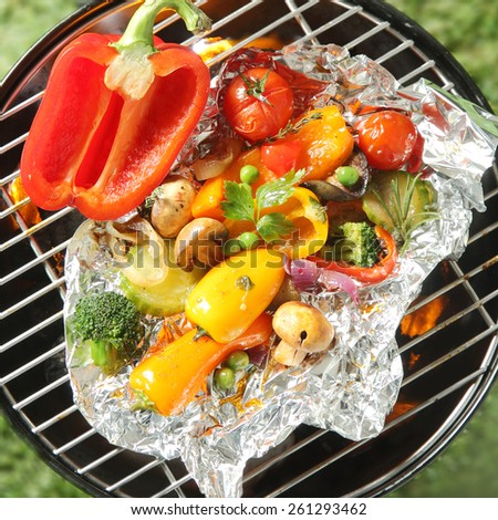 Healthy organic vegetarian and vegan cuisine with an assortment of farm fresh vegetables grilling in tin foil over the heat of a barbecue fire - stock photo