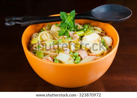 Healthy pasta dish with peas, leeks and bacon, with a garnish of fresh oregano, in an orange bowl with wooden serving spoon, on a dark wooden table - stock photo