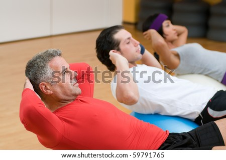 Healthy people with mature instructor doing sit-ups on fitness ball at gym - stock photo