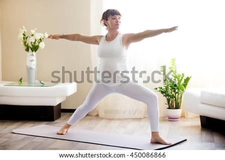 Healthy Pregnancy Yoga and Fitness concept. Young pregnant yoga woman working out in cozy living room interior. Pregnant model doing prenatal warrior II, virabhadrasana two yoga pose