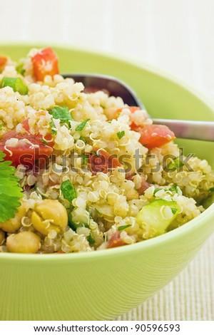 Healthy Quinoa salad in bright green bowl closeup - stock photo