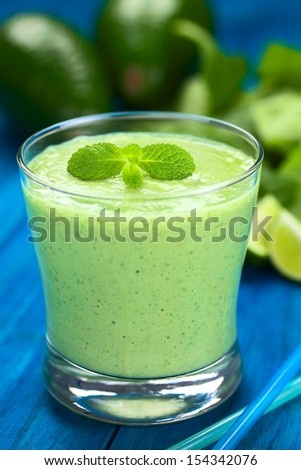 Healthy refreshing green smoothie made of fresh avocado, spinach, lime and yogurt garnished with mint and served in a glass on blue wood (Selective Focus, Focus on the big mint leaves on the drink) - stock photo