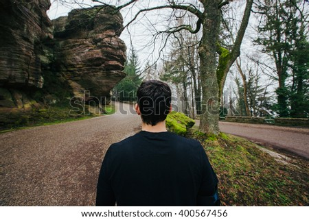 Healthy running runner man back choosing the path for running workout on mountain road. Jogging male fitness model working out training  on forest road. - stock photo