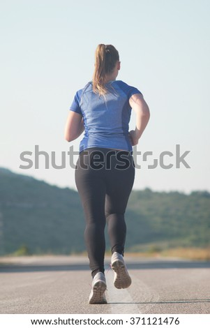 Healthy running runner woman early morning sunrise workout  mountain road workout jog - stock photo