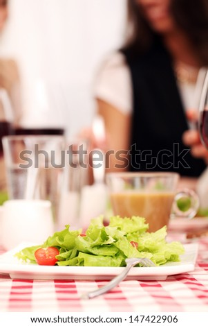 Healthy salad and red wine in a restaurant on a squared tablecloth