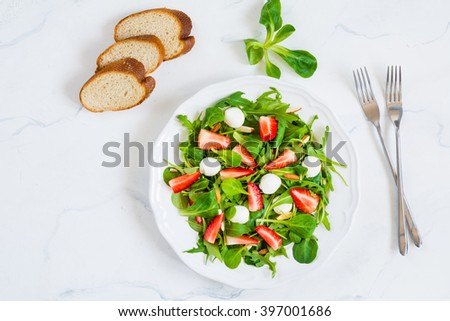 Healthy salad with arugula, spinach, strawberries, almonds and mini mozzarella cheese balls on plate on white background, table top view food. Flat lay food - stock photo