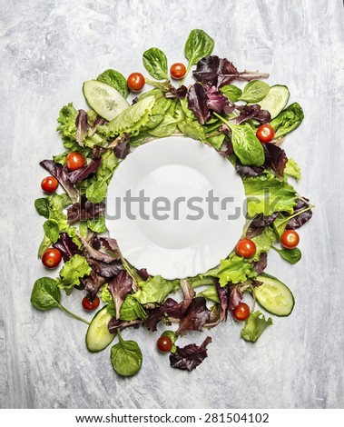Healthy salad with cucumber and tomatoes around white  empty plate, on light gray wooden background, top view, copy space - stock photo