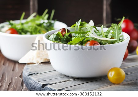 Healthy salad with rocket, tomato and parmesan cheese, selective focus
