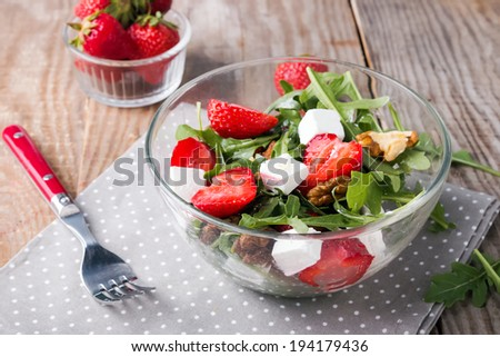 Healthy salad with strawberries and arugula in glass bowl on the table - stock photo
