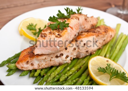 healthy salmon with coriander garnished with asparagus and lemon - stock photo