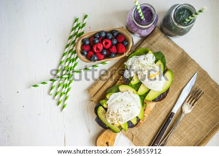 Healthy sandwich with avocado and poached eggs - stock photo