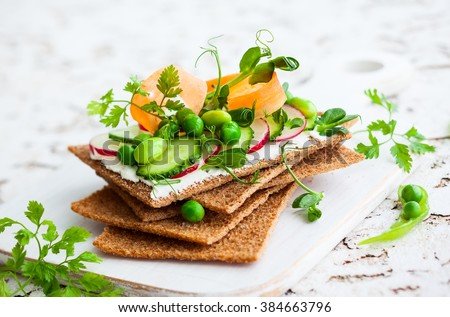 Healthy sandwiches with soft cheese and raw spring vegetables on crisp rye bread - stock photo