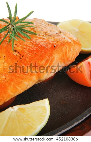 healthy sea food: grilled salmon on iron pan over wooden plate with lemon avocado and tomatoes isolated on white background - stock photo