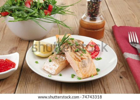 healthy sea food : roasted pink salmon fillet with vegetable salad , chives, lemon, red caviar in white bowl, with pepper in grinder and cutlery on white dish over wooden table - stock photo