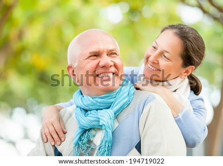 Healthy senior man and mature woman against blured trees of park or forest