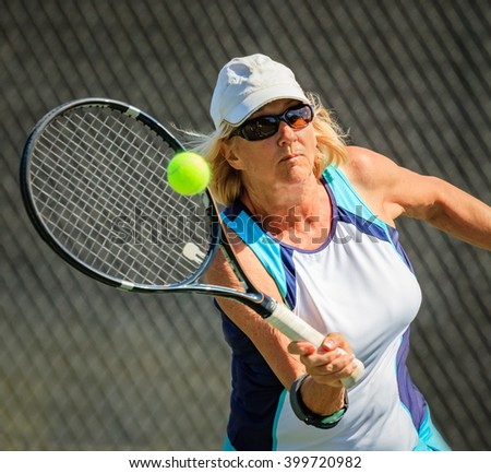 Healthy senior woman playing tennis - stock photo