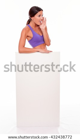Healthy shouting brunette woman standing behind a blank placard and looking at camera one hand to her cheek while wearing violet gymnastic clothing isolated - stock photo