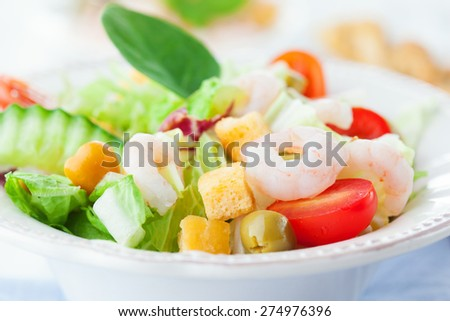 Healthy shrimp salad with mixed greens, olives and tomatoes on white wooden background, selective focus - stock photo