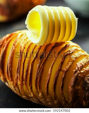 Healthy sliced baked potato cooked with the jacket on in foil and served topped with a creamy butter curl on a dark background, close up view - stock photo