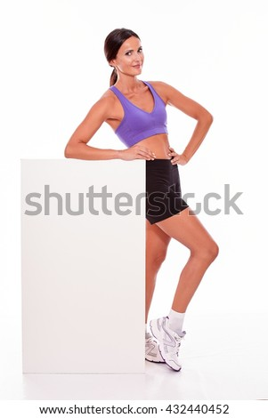 Healthy smiling brunette woman holding blank placard and looking at camera with one hand on her hip while wearing violet and black gymnastic clothing, isolated - stock photo