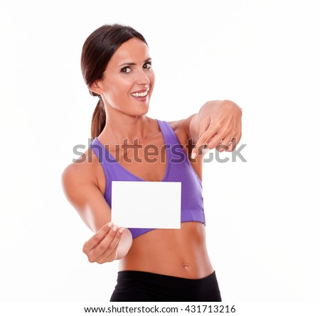 Healthy smiling brunette woman, pointing at copy space she is holding while looking at camera and wearing violet and black gymnastic clothing, isolated - stock photo
