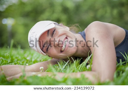 Healthy smiling young woman lying on green grass. Enjoy nature.  - stock photo