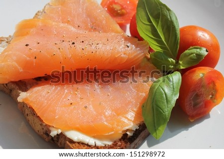 Healthy smoked salmon on toast with cream cheese, basil, and cherry tomato's - stock photo