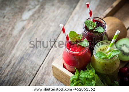 Healthy smoothie from kiwi, raspberries and blueberries in a jars with straws and mint leaves in wooden box on table with copy space. - stock photo