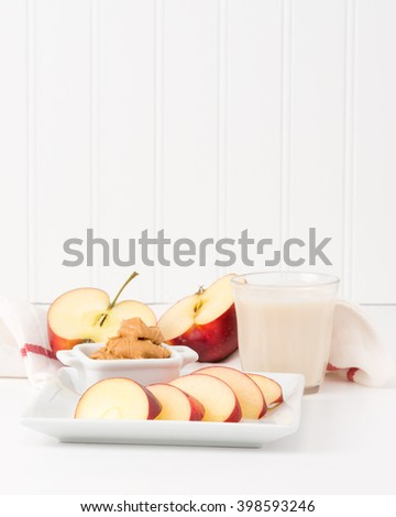 Healthy snack of fresh red apples and peanut butter with a glass of milk. - stock photo