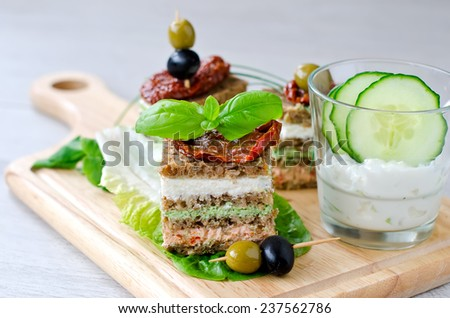 Healthy snack pieces of bread with cottage and antipasto on cutting board - stock photo