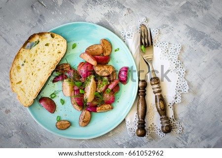 Healthy snack - roasted radishes with herbs and delicious italian bread. Top view.