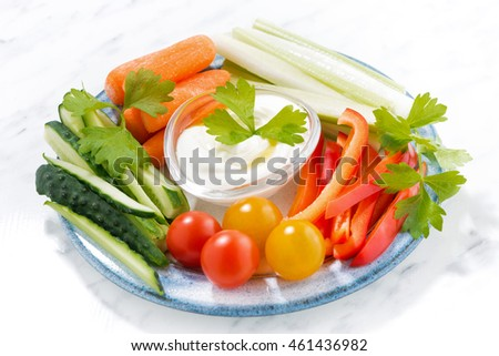 healthy snacks, mixed fresh vegetables and yogurt on a plate, closeup, horizontal