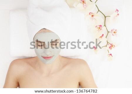 Healthy spa: young beautiful relaxing woman having moistening mask - stock photo