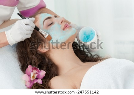 Healthy Spa: Young Beautiful Relaxing Woman Having Moistening Mask Applied - stock photo