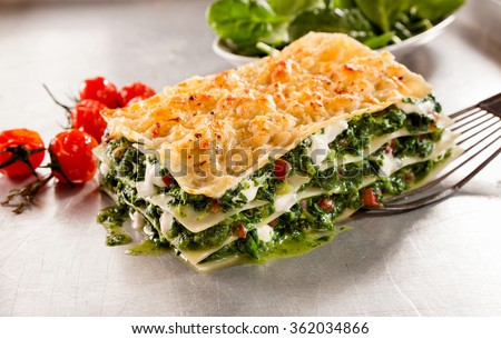 Healthy spinach and cheese Italian lasagne topped with crispy cheese with roasted tomatoes served on a spatula for a tasty lunch or meal - stock photo
